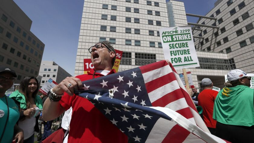 Nurse Kevin-Marc Ramos joins fellow labor union members in a protest outsuide the Ronald Reagan Medical Center at UCLA.