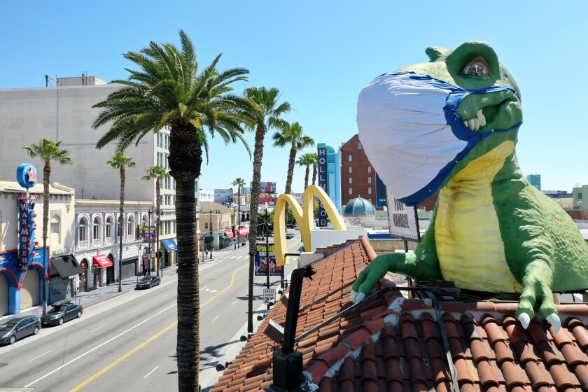 A giant T-Rex wearing a protective mask sends a coronavirus message to a mostly empty intersection of Hollywood Blvd. and Highland Ave. from the top of Ripley's Believe It or Not! Odditorium, which is temporarily closed.