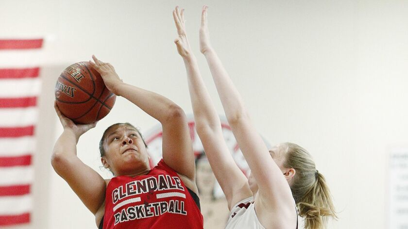 Glendale's Melissa Zamora turns to take a shot against La Canada's Amanda Scoville who reaches to bl
