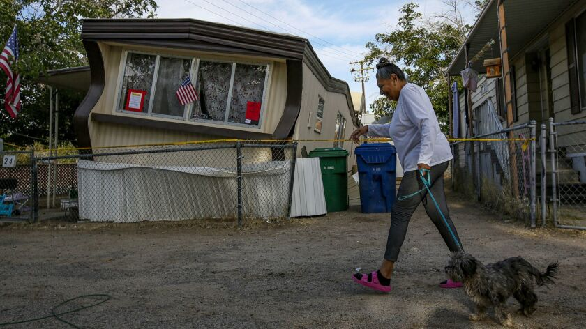 Carmen Rivera on a morning walk with her dog Ash passes by a mobile home dislodged in Torusdale Estates mobile home park.