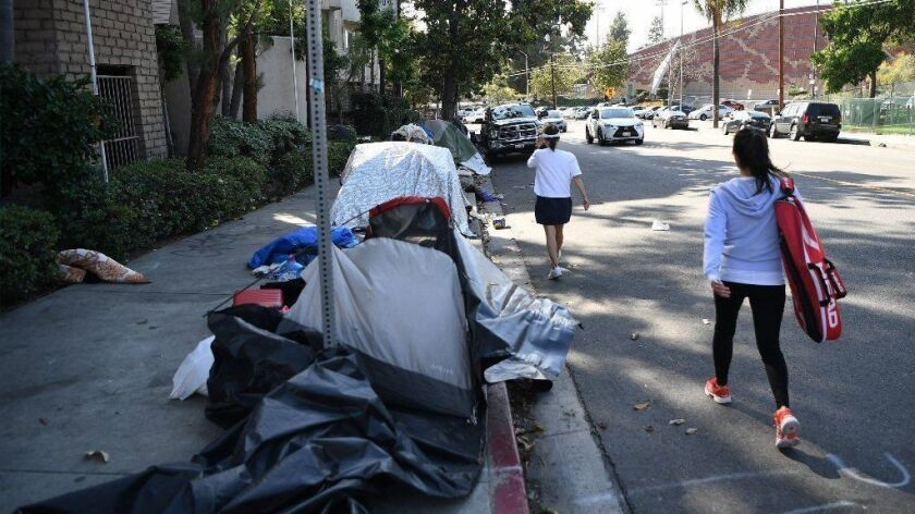 Pedestrians walk in the street to bypass tents set up by homeless people on a Koreatown sidewalk.