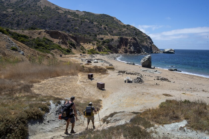 Hikers arrive at a campground at the beach