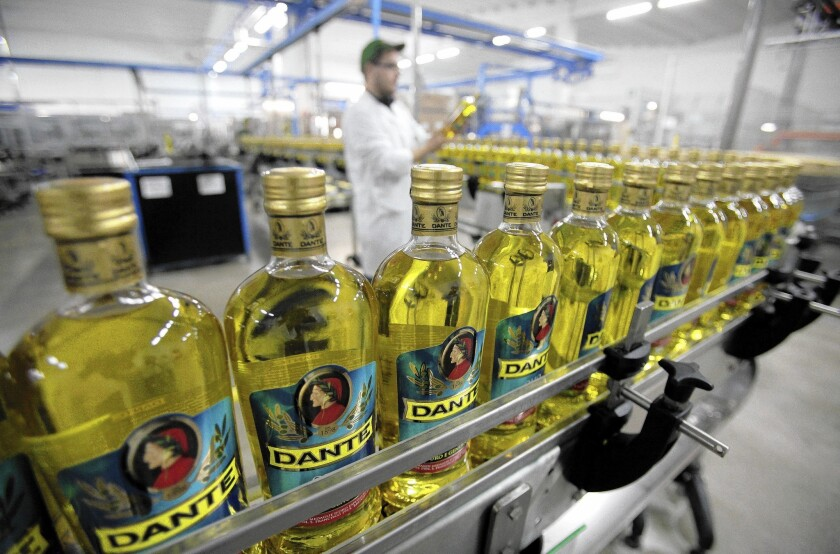 An employee checks a bottle of Dante olive oil as it travels along the production line at a factory in Montesarchio, Italy. New standards proposed in California would apply only to the largest California olive growers and millers.