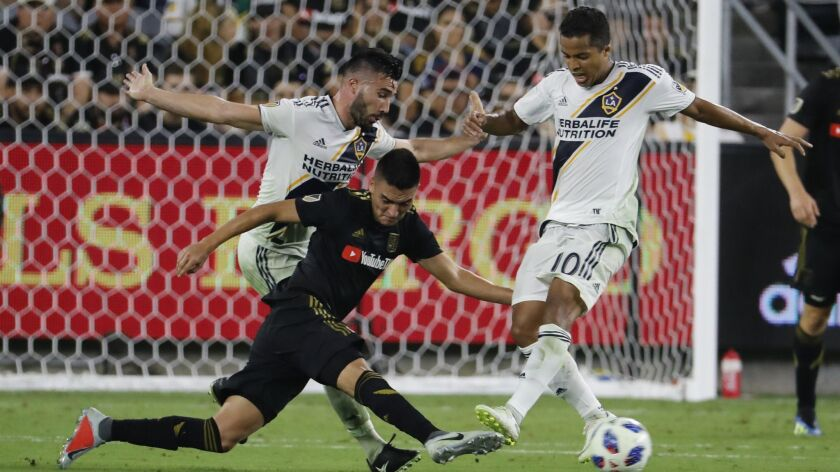Galaxy midfielder Romain Alessandrini, left, and forward Giovani dos Santos, right, battle LAFC midfielder Eduard Atuesta, center, for control of the ball in the second half on July 26, 2018.