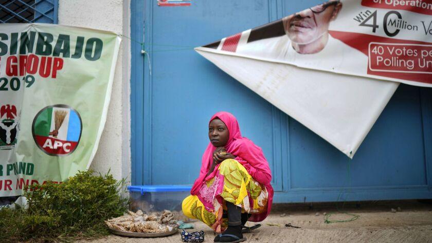 A woman sells peanuts outside President Muhammadu Buhari's campaign headquarters in Abuja, Nigeria, on Feb, 26, 2019.