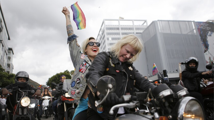 <p>Kristen Wright, 36, thrusts a gay pride flag into the sky as Ashley Boyd, 30, rides a motorcycle