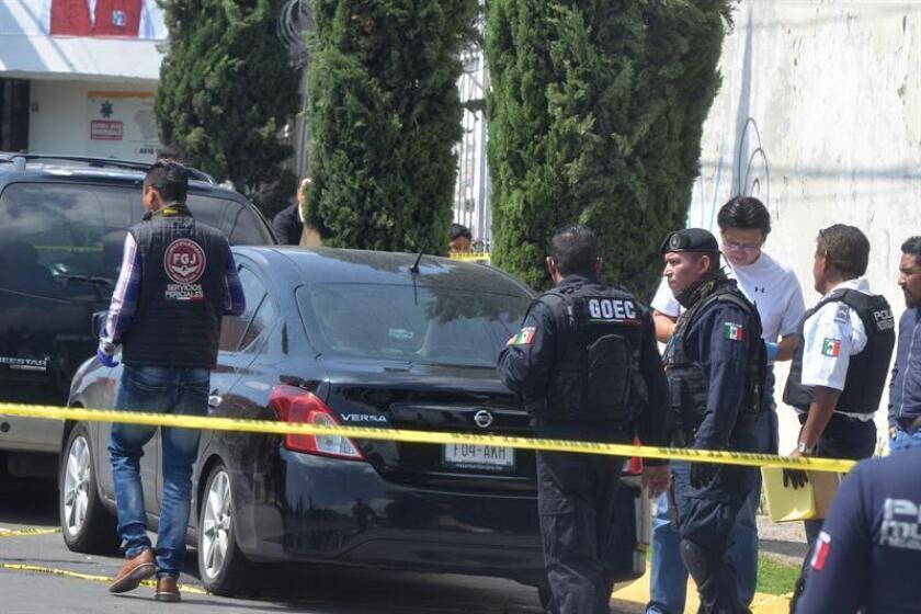 Peritos forenses recaban información en torno del auto donde 6 personas fueron halladas sin vida en un populoso barrio del municipio de Nezahualcoyotl, en el Estado de México (México). EFE