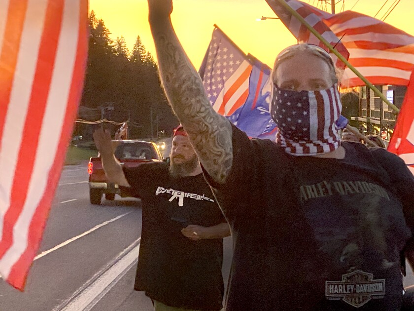 People wave U.S. and Trump campaign flags at a protest
