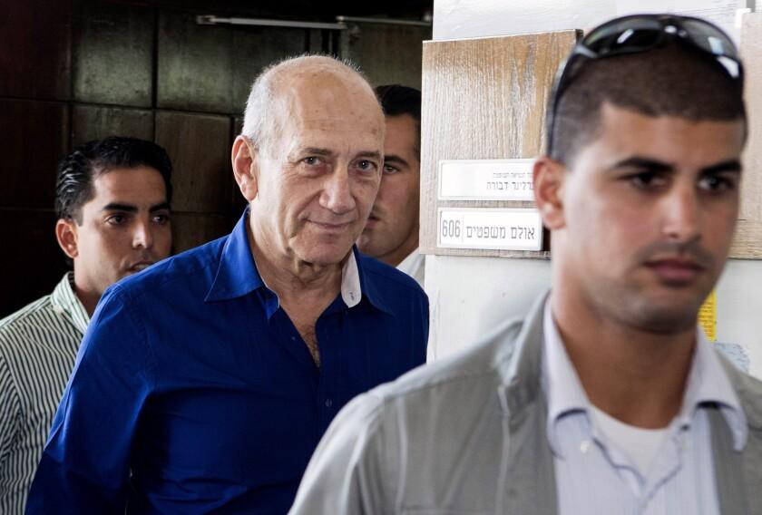 Former Israeli Prime Minister Ehud Olmert, center, leaves Tel Aviv District Court after receiving a prison sentence on a bribery conviction.