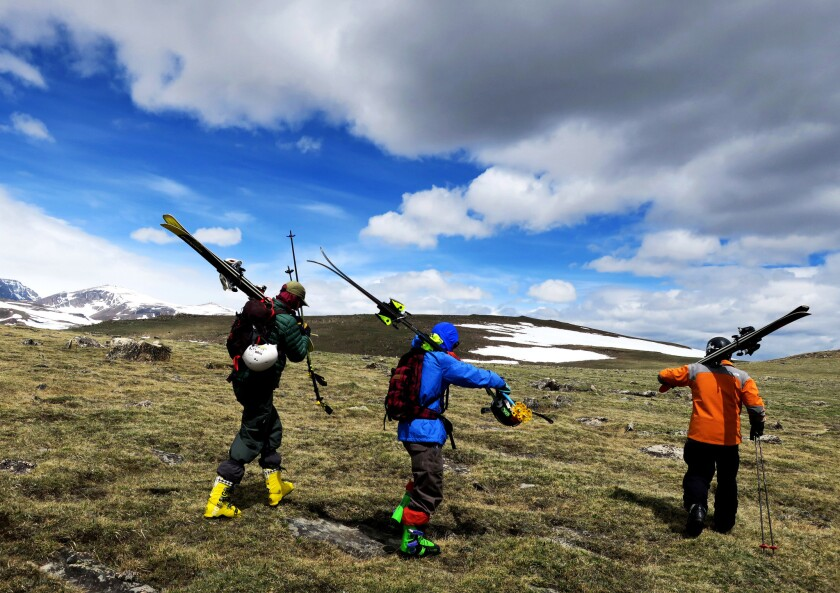 Skiers hike across the plateau to the Rock Creek Headwall along the Beartooth Highway.