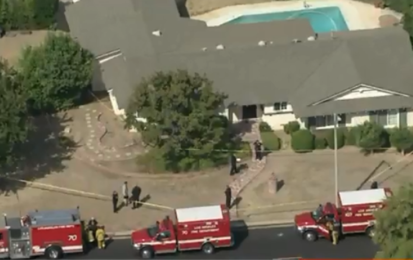 Police respond to the scene of a Northridge home where three people were shot.