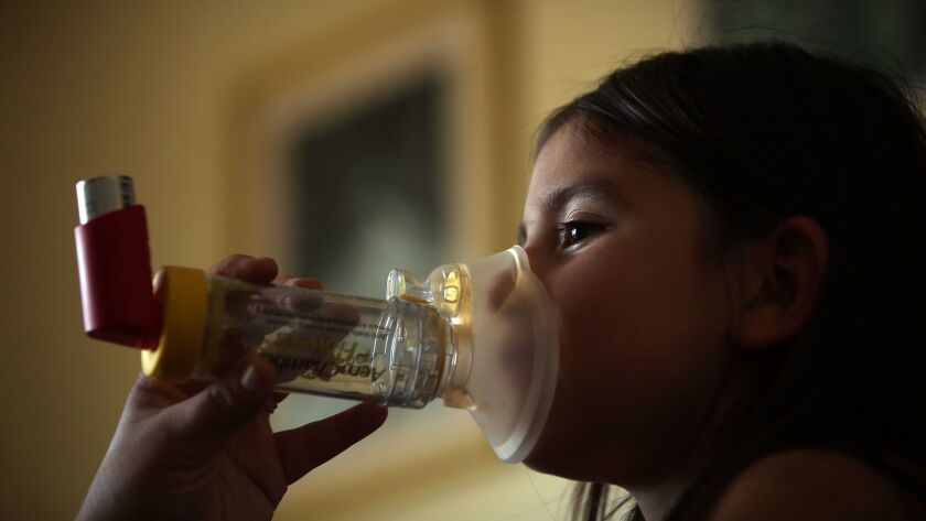 A 6-year-old uses an inhaler to help ease her asthma symptoms. Asthma is one of the health conditions projected to increase as the planet gets warmer, experts say.