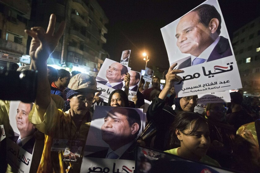 Supporters of Egyptian presidential candidate Abdel Fattah Sisi hold signs as they watch him on a screen during his first television interview.