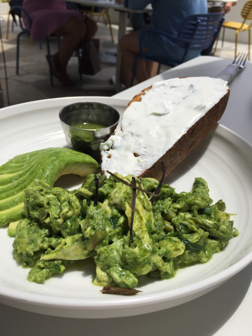 Organic green scrambled eggs at Parakeet Cafe. The dish includes kale, asparagus, green beans, avocado and salsa verde with a side of toast with labneh spread.