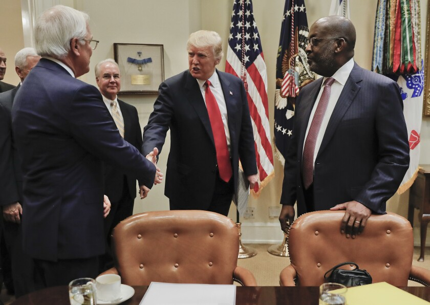 FILE - In a Monday, Feb. 27, 2017 file photo, President Donald Trump, greets Independence Blue Cross and Health CEO Joseph R. Swedish, left, and Kaiser Permanente CEO Bernard J. Tyson, right, during a meeting with health insurance company executives, in the Roosevelt Room of the White House. Health care provider Kaiser Permanente says its chairman and CEO, Bernard Tyson, died unexpectedly Sunday, Nov. 10, 2019 at the age of 60. No other details were provided in the company's announcement, which said that Tyson died in his sleep early Sunday. (AP Photo/Pablo Martinez Monsivais, File)