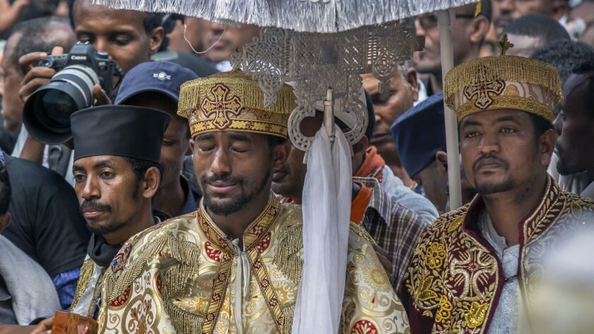A priest cries at a mass funeral at the Holy Trinity Cathedral in Addis Ababa, Ethiopia Sunday, Marc