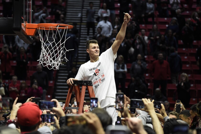 SDSU forward Yanni Wetzell holds up a piece of the net after the team defeated New Mexico to clinch the Mountain West regular-season title on Feb. 11.