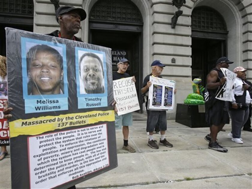 In this Tuesday, Aug. 13, 2013 photo shows Cleveland residents holding up signs in protest of the Cleveland Police Department  in Cleveland. Months of disciplinary hearings and racially charged complaints against police has set the scene for outside investigations focused in part on a chase that ki