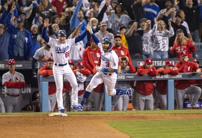 Chris Taylor pumps a fist as he rounds first base. Behind him, Cardinals players stand in the dugout looking dejected.