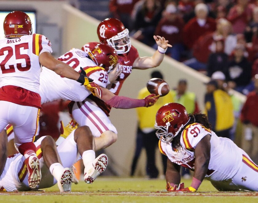 Oklahoma quarterback Baker Mayfield (6) fumbles the ball as Iowa State linebacker Kane Seeley (29) reaches for the recovery during the first quarter of an NCAA college football game in Norman, Okla., on Saturday, Nov. 7, 2015. (AP Photo/Alonzo Adams)