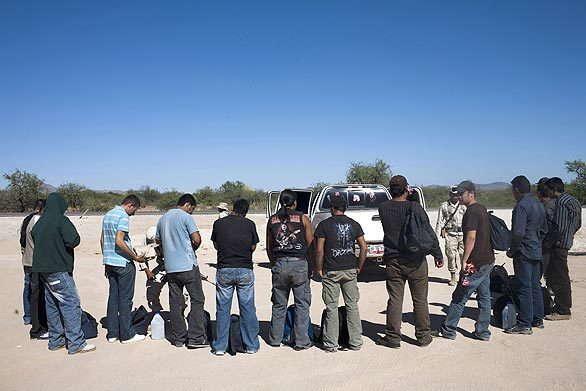 A group of migrants is searched by Mexican soldiers near Sasabe, Mexico. In Mexico's northern Sonora state, migrants and drug smugglers both look to make the difficult journey into the U.S. Tougher border enforcement has pushed the groups, once separate, into the same obscure parts of the desert. The close company adds a new element of danger to migrants' already perilous journey.