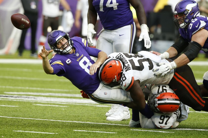 Minnesota Vikings quarterback Kirk Cousins (8) passes as he is tackled by Cleveland Browns defensive tackle Malik Jackson (97) and defensive tackle Malik McDowell (58) during the second half of an NFL football game, Sunday, Oct. 3, 2021, in Minneapolis. The Browns won 14-7. (AP Photo/Bruce Kluckhohn)