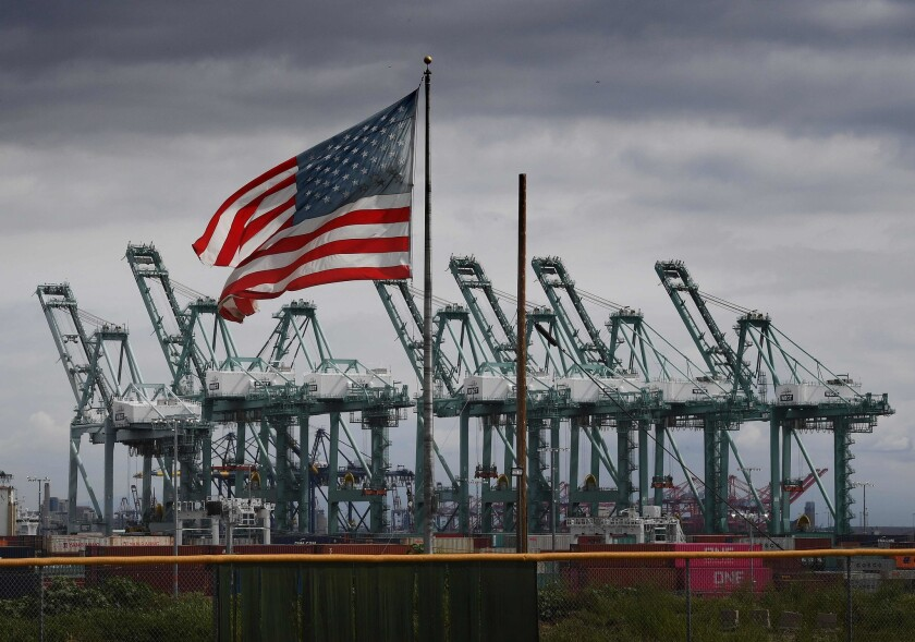 The U.S. flag flies over shipping cranes and containers at the Port of Long Beach.