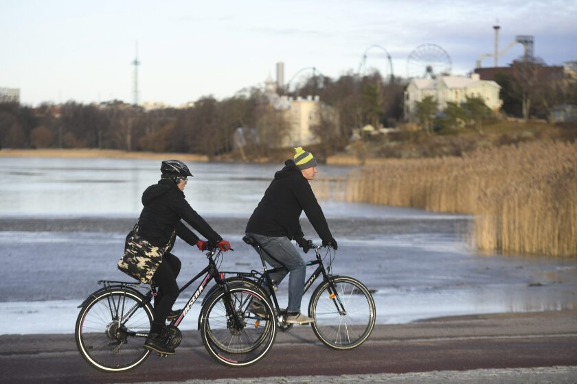 """In this photo taken on Wednesday, Jan. 1, 2020, cyclists enjoy a sunny day in Helsinki. Unusually mild weather in Finland left the southern part of the Nordic nation with a surprising absence of snow and an unusual delay in the start of """"thermal winter,"""" meteorologists said. Mainland Finland recorded a high temperature of 7.9 degrees Celsius (46.2 F) and it reached 8.7 degrees Celsius (47.7 F) in the Aland Islands, an autonomous Baltic Sea region of Finland. (Vesa Moilanen/Lehtikuva via AP)"""