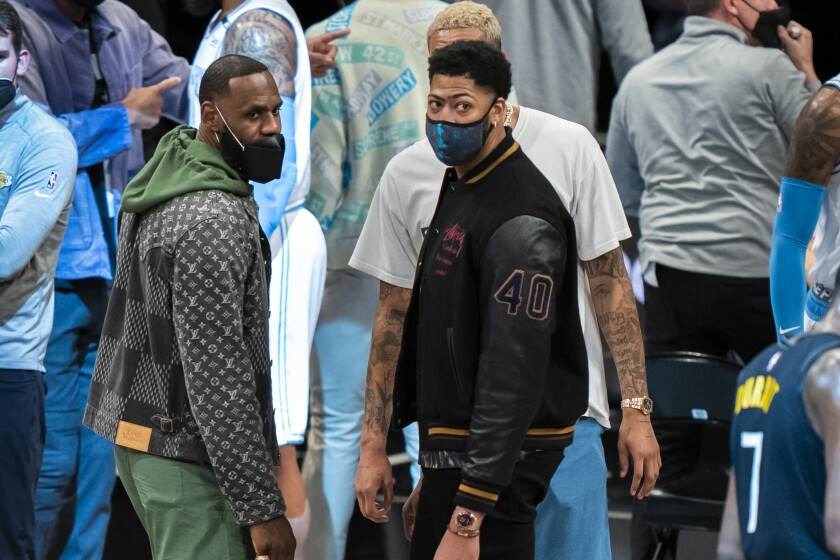 Lakers forwards LeBron James and Anthony Davis stand near the team during a timeout.