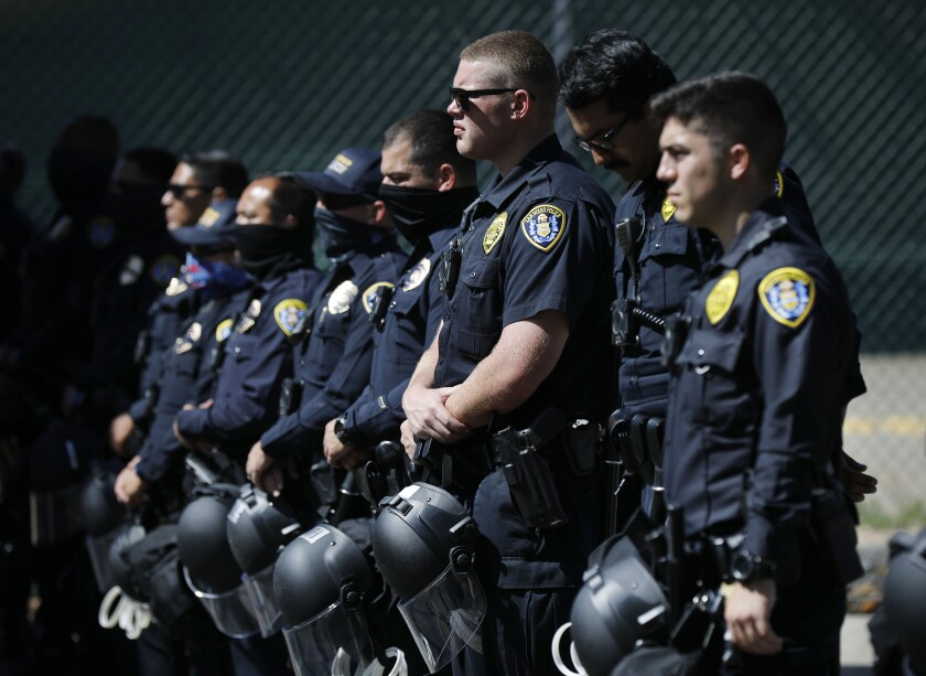 San Diego police officers stand near police headquarters as a racial justice protesters gather in the area on June 14, 2020.