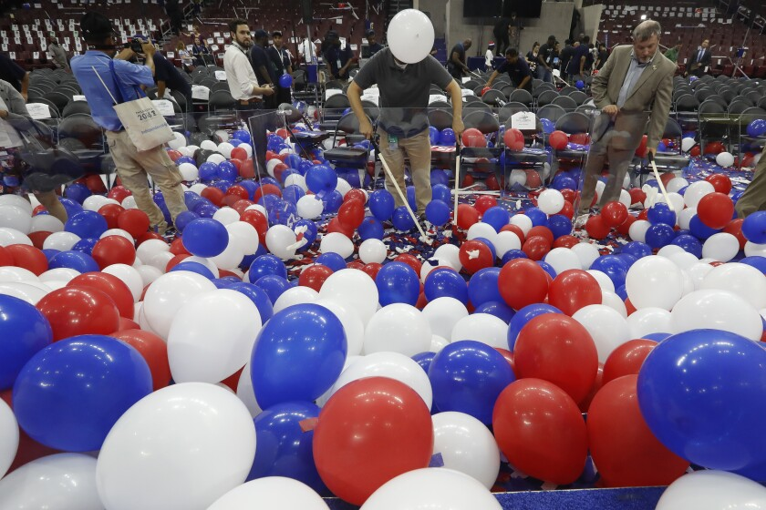 Confetti and balloons cover the stage as a worker begins to clean up after the 2016 Democratic National Convention.