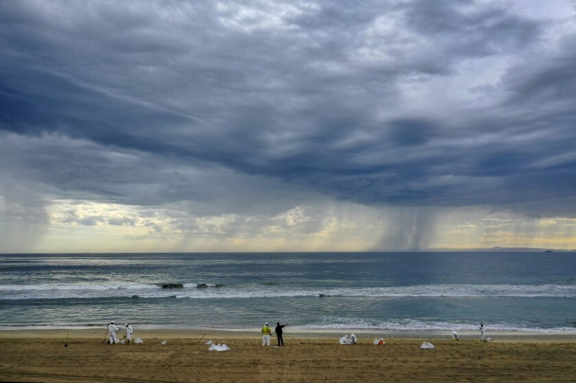 A storm rolls in as cleanup crews spread out across Huntington State Beach.