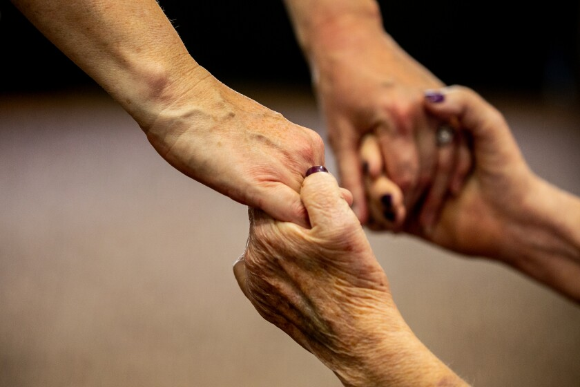 Mother and daughter grasp hands as they meet at St. Paul's Senior Services Nursing and Rehabilitation Center.