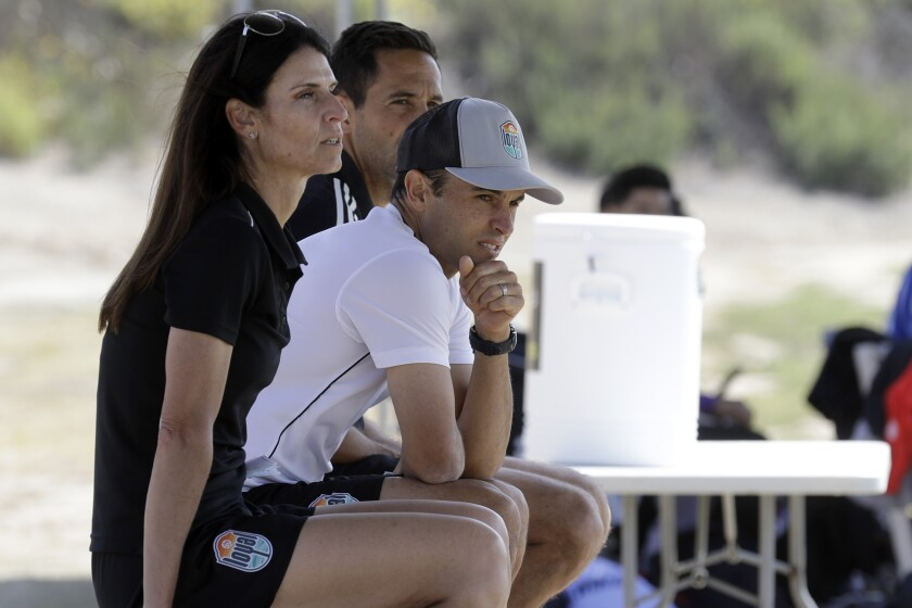 Landon Donovan sits between assistant coaches Nate Miller and Carrie Taylor during a scrimmage on Wednesday in Chula Vista.