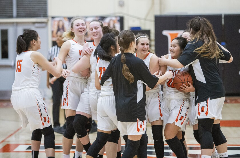 Huntington Beach players celebrate after beating Aliso Niguel 53-48 in the first round of the CIF Southern Section Division 1 playoffs at home Thursday.