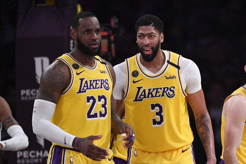 Lakers forward LeBron James, left, stands with forward Anthony Davis during a game Feb. 21, 2020