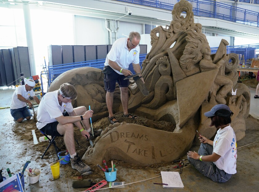 """Team members with Archisand Professional Sand Sculpture put the final touches of their sculpture, titled """"Dreams Take Flight."""""""