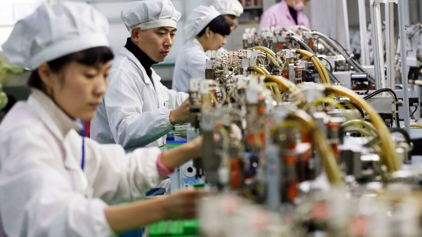 In this Dec. 8, 2017 photo, workers assemble micromotors at a factory in Huaibei in central China's