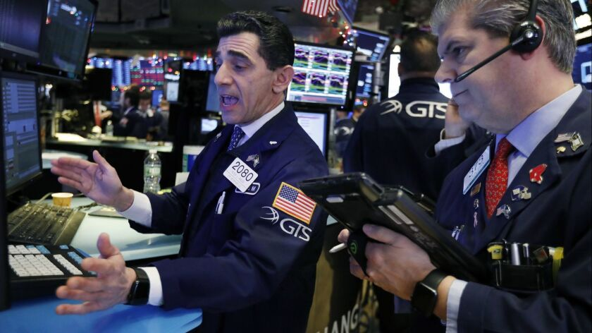 Specialist Peter Mazza, left, and trader John Panin work on the floor of the New York Stock Exchange on Dec. 6.