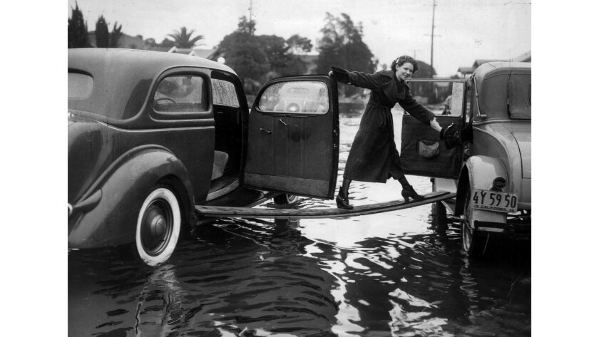 Feb. 11, 1936: After her car stalled out in curb-deep water, a friend of Helen Lawrence found a plank to serve as a bridge to another car.