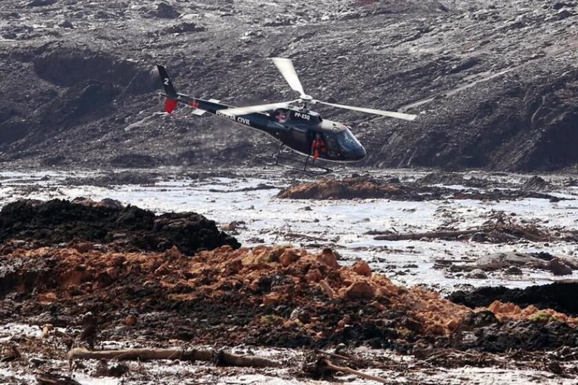 A helicopter looks for survivors after the rupture of a tailings dam on Jan. 25, 2019, at a mine owned by Vale, the world's largest iron-ore producer. The mine is located in Brumadinho, a municipality of the southeastern Brazilian state of Minas Gerais. EPA-EFE/PAULO FONSECA