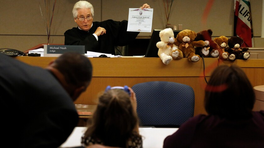 Judge shows a certificate of family membership to a family who legally adopted a child in 2014.