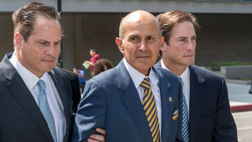 Former Los Angeles County Sheriff Lee Baca, center, walks with attorneys, David Hochman, left, and N