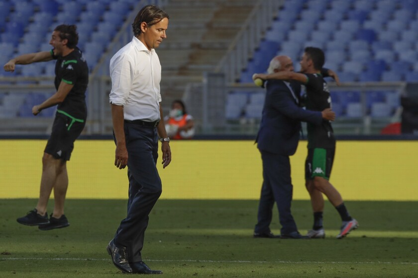 Lazio's head coach Simone Inzaghi walks off the pitch past Sassuolo's celebrating players, at the end of the Serie A soccer match between Lazio and Sassuolo at the Rome Olympic Stadium Saturday, July 11, 2020. Sassuolo won 2-1. (AP Photo/Alessandra Tarantino)