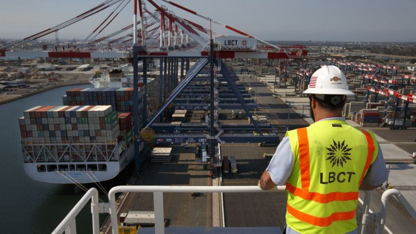 A worker with the Long Beach Container Terminal watches a container ship being unloaded.