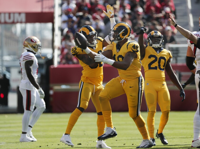 Rams linebacker Trevon Young (49) shows off the football to teammates Troy Hill and Lamarcus Joyner (20) after intercepting a pass in the first half against the San Francisco 49ers on Sunday in Santa Clara.