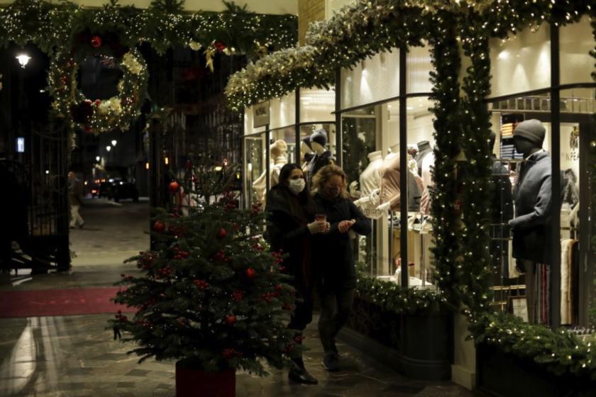Unas mujeres con cubrebocas por el coronavirus pasan frente a una tienda de ropa