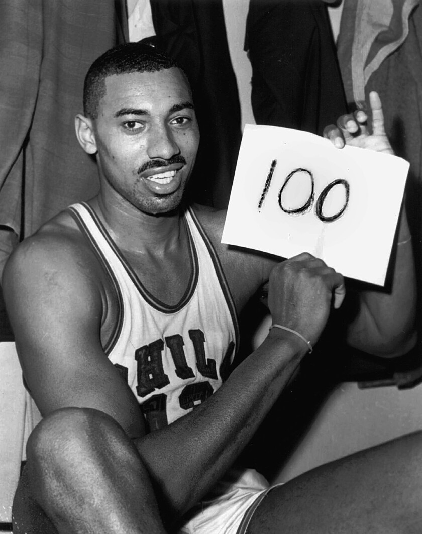 """On March 2, 1962, Wilt Chamberlain of the Philadelphia Warriors holds a sign reading """"100"""" after he scored 100 points."""