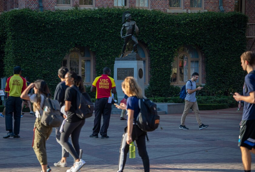 Several USC students walk by Tommy Trojan in November 2019.