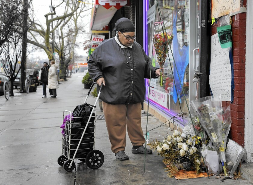 A woman places flowers at a memorial for Eric Garner on Dec. 3 near where he died in Staten Island, N.Y.